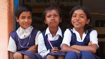 Indian schoolgirls sit on the step outside their classroom at their poor village school outside Bandhavgarh National Park. They are wearing a school uniform. The three little girls are friends.