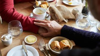 Male couple holding hands at restaurant table, hands detail