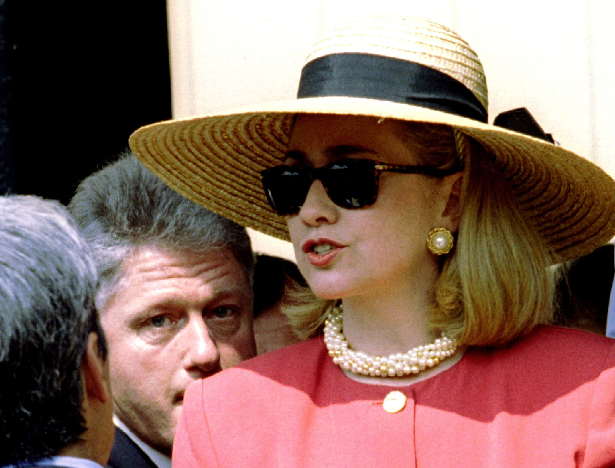 President Clinton (L) peers underneath the wide-brimmed hat of wife Hillary, after the dedication of an affordable housing project, in Little Rock June 25