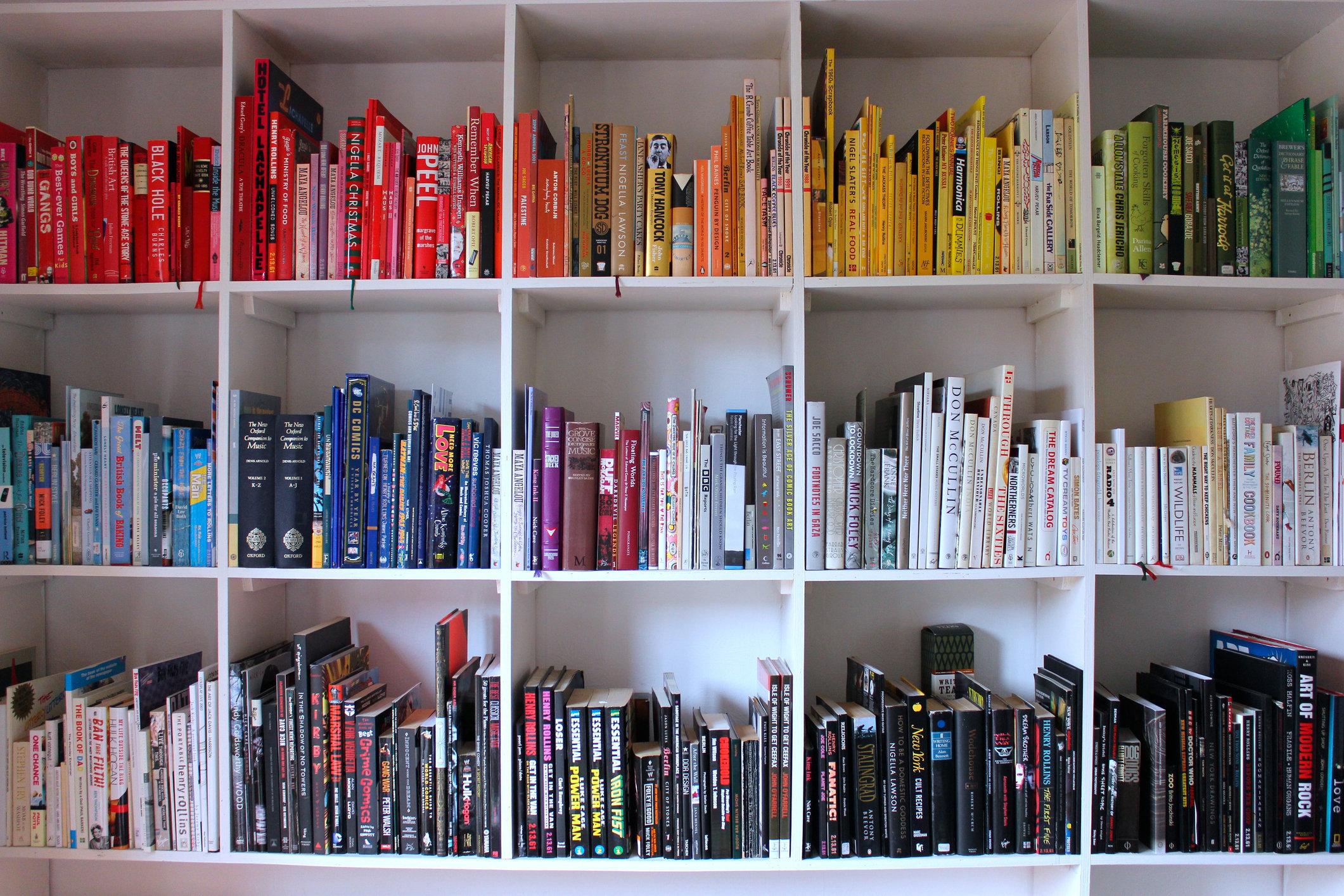 Books on white shelves arranged in rainbow coloured order.