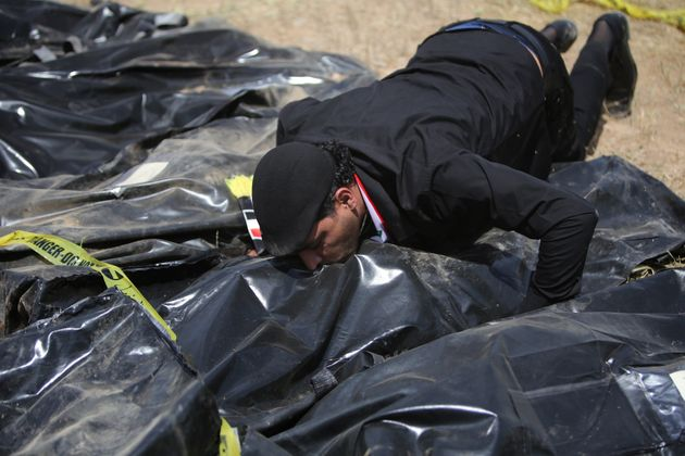 An Iraqi man kisses a body-bag lying amidst other bags containing the remains of people believed to have...