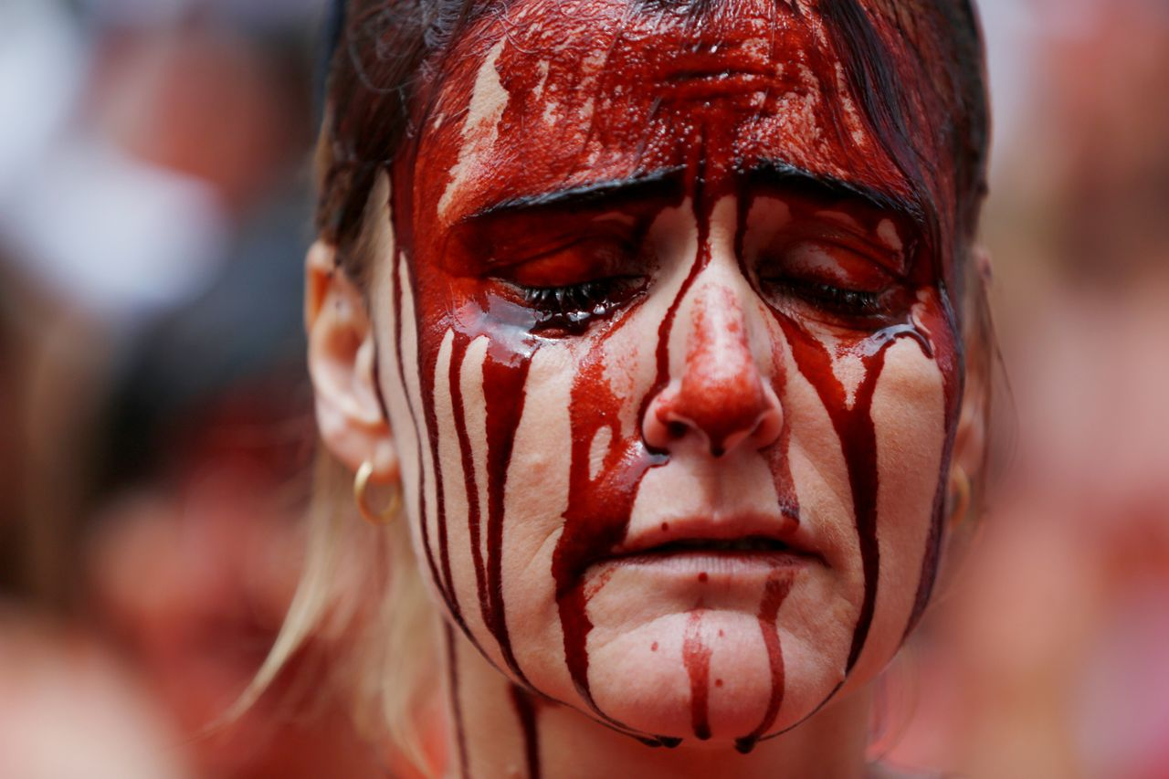 A day before the start of the running of the bulls San Fermin festival in Pamplona, northern Spain, activists grab buckets of blood to express their anger with the practice of bullfighting.