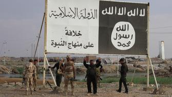Iraqi government forces gather under a billboard bearing slogans of the Islamic State (IS) group and its trademark flag, in the town of Heet, in Iraq's Anbar province, which they are battling to retake from IS jihadists, on April 7, 2016.   Earlier in the month Iraqi security forces recaptured parts of Heet, which was one of the largest population centres in Anbar province still held by the Islamic State (IS) group, but other areas remain under jihadist control.    / AFP / MOADH AL-DULAIMI        (Photo credit should read MOADH AL-DULAIMI/AFP/Getty Images)