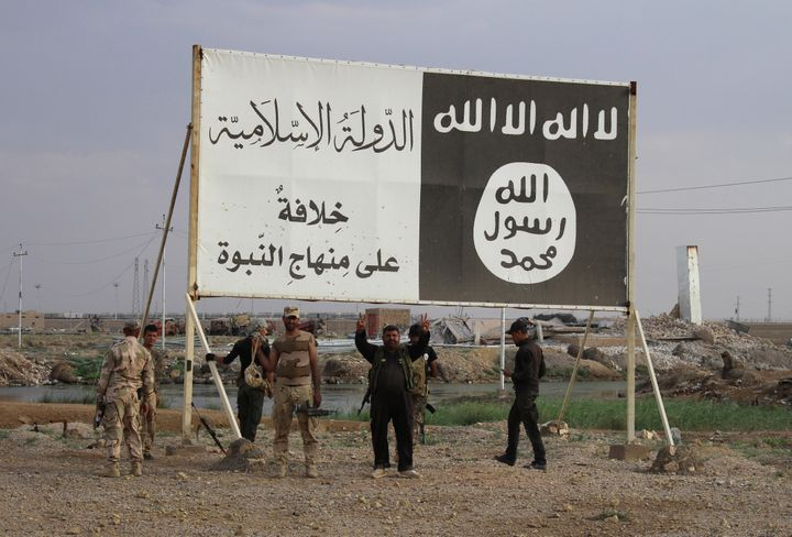 Iraqi government forces gather under a billboard bearing slogans of the Islamic State group inIraq's Anbar province on