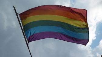 Gay pride rainbow flag nicely curved in the wind with a blue sky