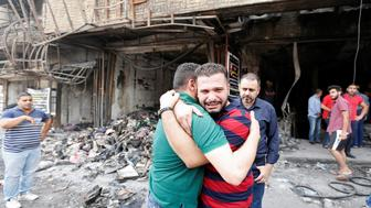 Iraqi men react at the site after a suicide car bomb attack at the shopping area of Karrada, a largely Shi'ite district, in Baghdad, Iraq July 4, 2016. REUTERS/Ahmed Saad
