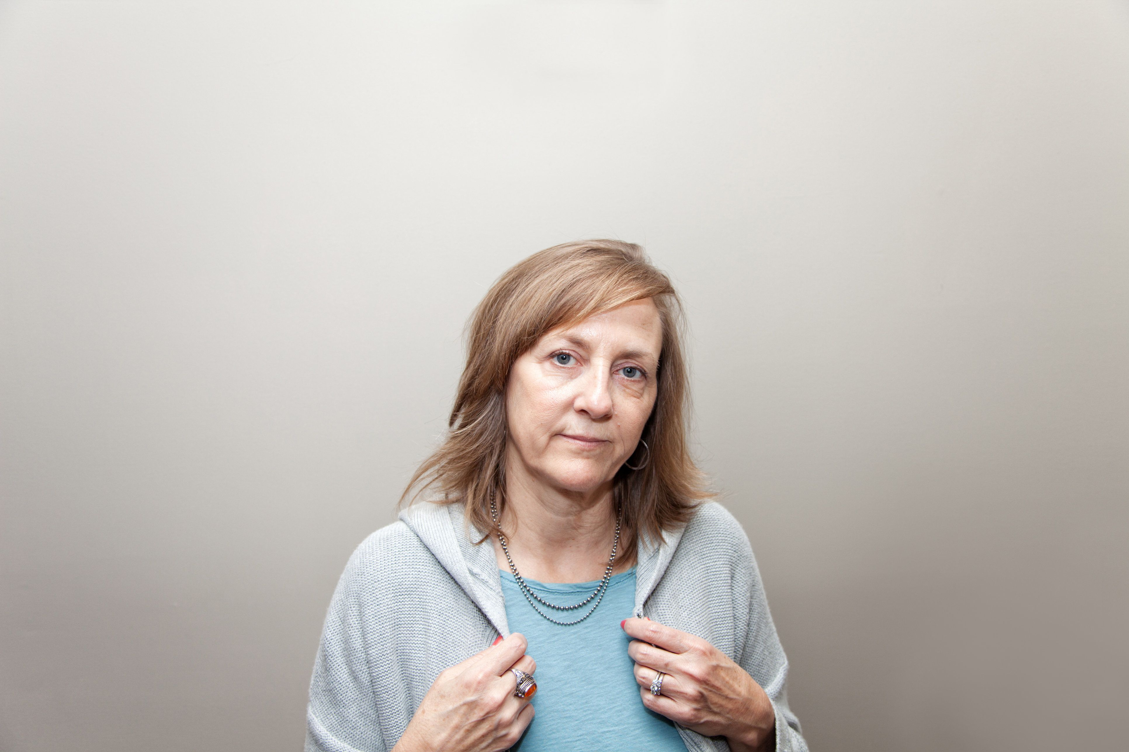 Mature female looking directly at camera, neutral expression, with hands visible; no makeup on 55 year old female with signs of aging