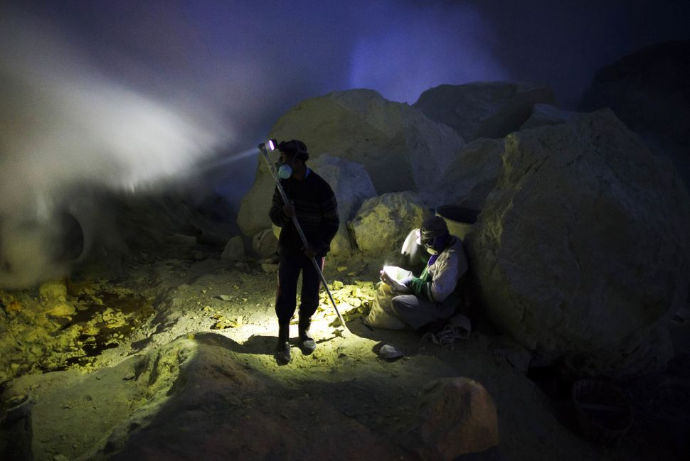 Miners extract lumps of sulfur from the Ijen volcano at night.