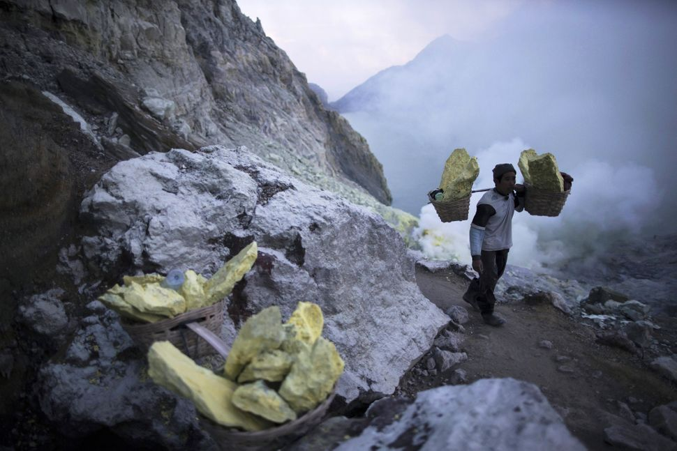 A miner carries baskets of sulfur as sulfuric gas rises from the volcano.