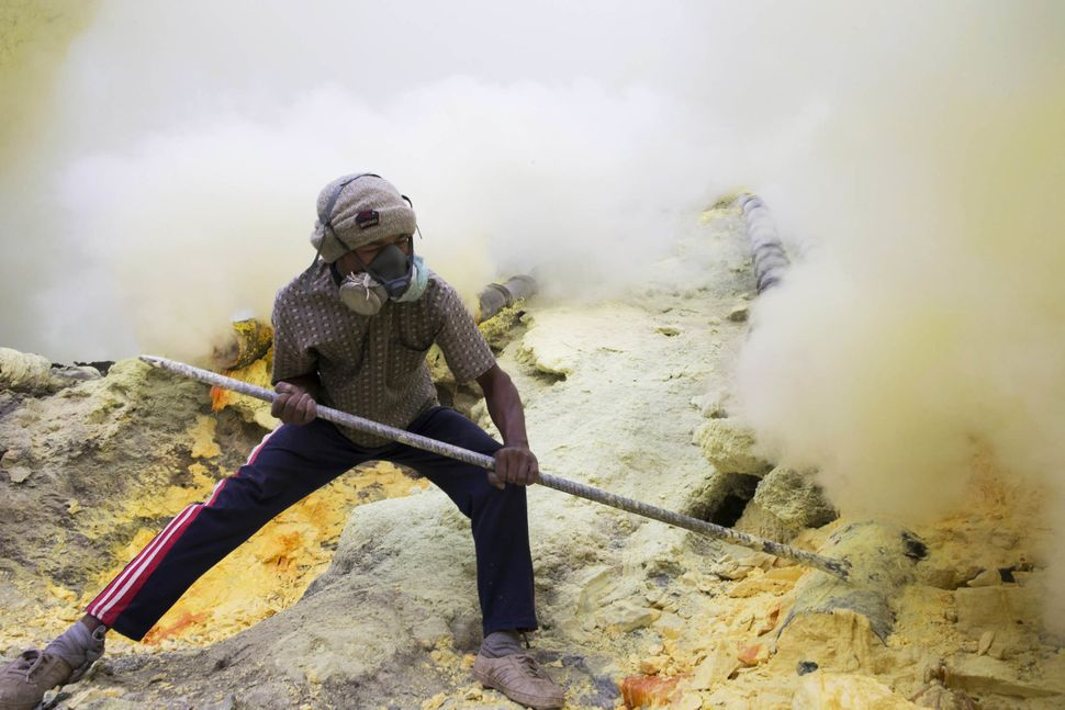 A miner uses a metal pole to extract lumps of sulfur as sulfuric gas rises from the Ijen volcano.