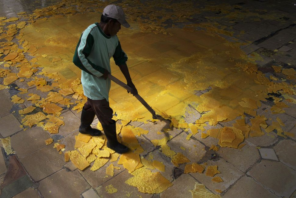 A worker breaks up a sheet of sulfur from the ground for collection at a processing facility in Banyuwangi.