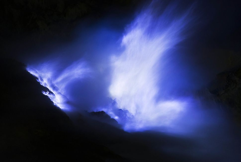 Ignited sulfuric gas, known as blue fire or blue frame, rises from ceramic pipes at the Ijen volcano at night.