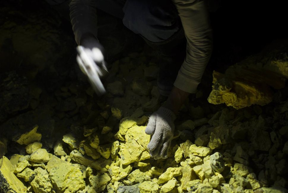 A miner uses a hammer to break lumps of sulfur at the Ijen volcano.
