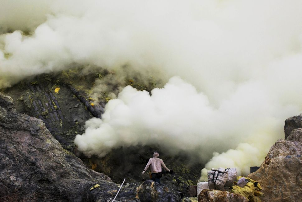 Miners work as sulfuric gas rises from the volcano.