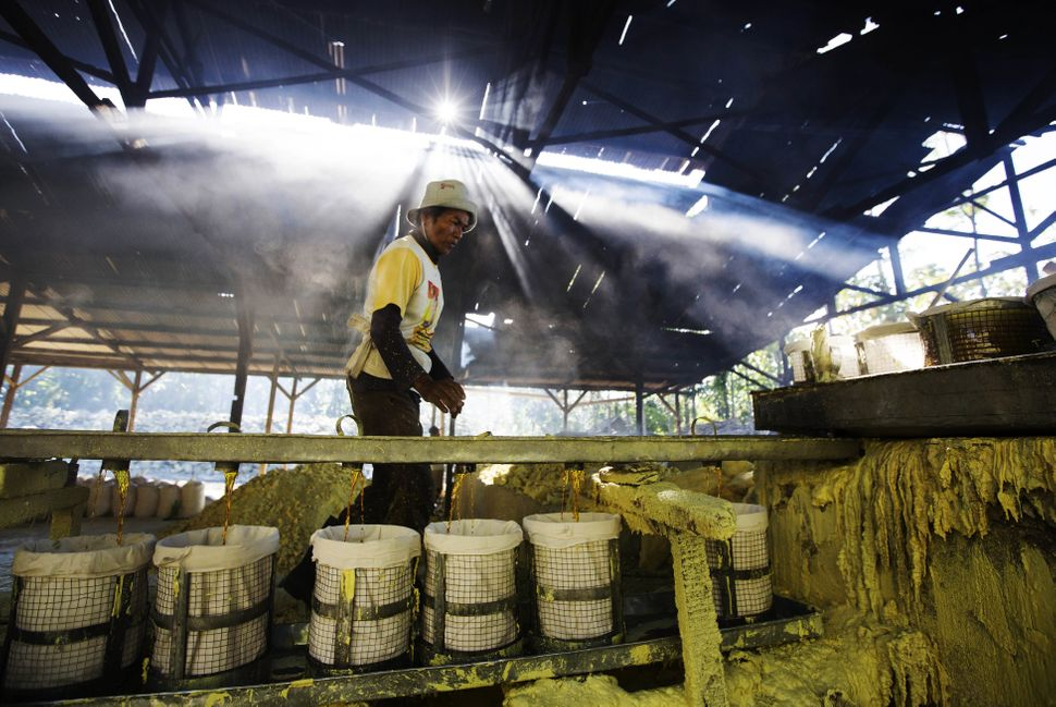 A worker observes liquid sulfur being filtered at a sulfur processing facility in Banyuwangi.