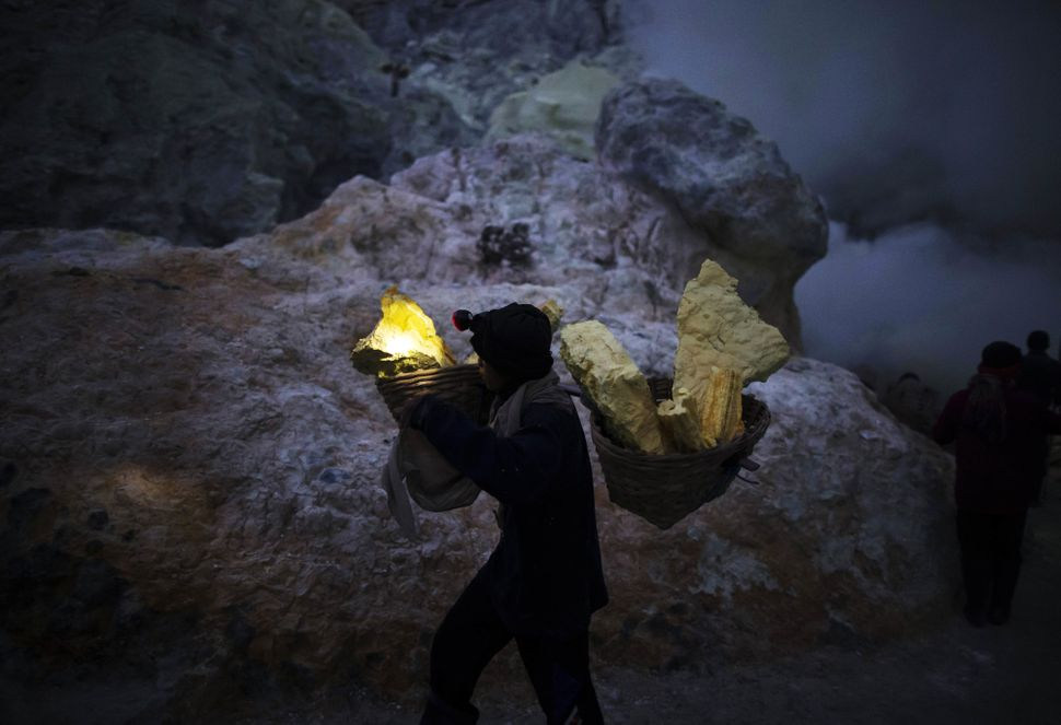 A miner carries baskets of sulfur at the Ijen volcano at night.