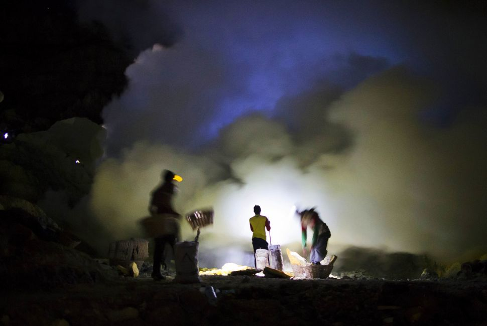Miners extract lumps of sulfuramid swirling clouds of sulfur dioxide and other gases.