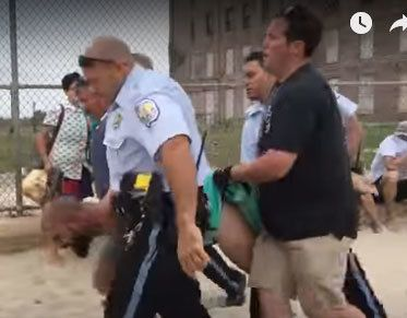 Fox is carried by police officers off the beach and placed under arrest