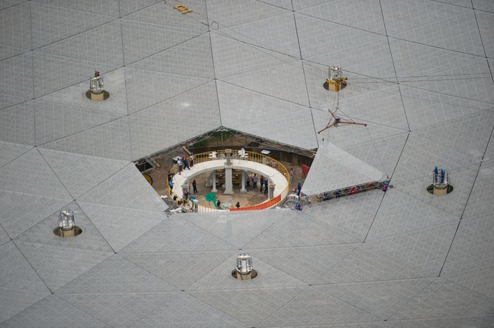 Workers lift the last panel to install into the center of a Five-hundred-meter Aperture Spherical Telescope (FAST) on July 3.