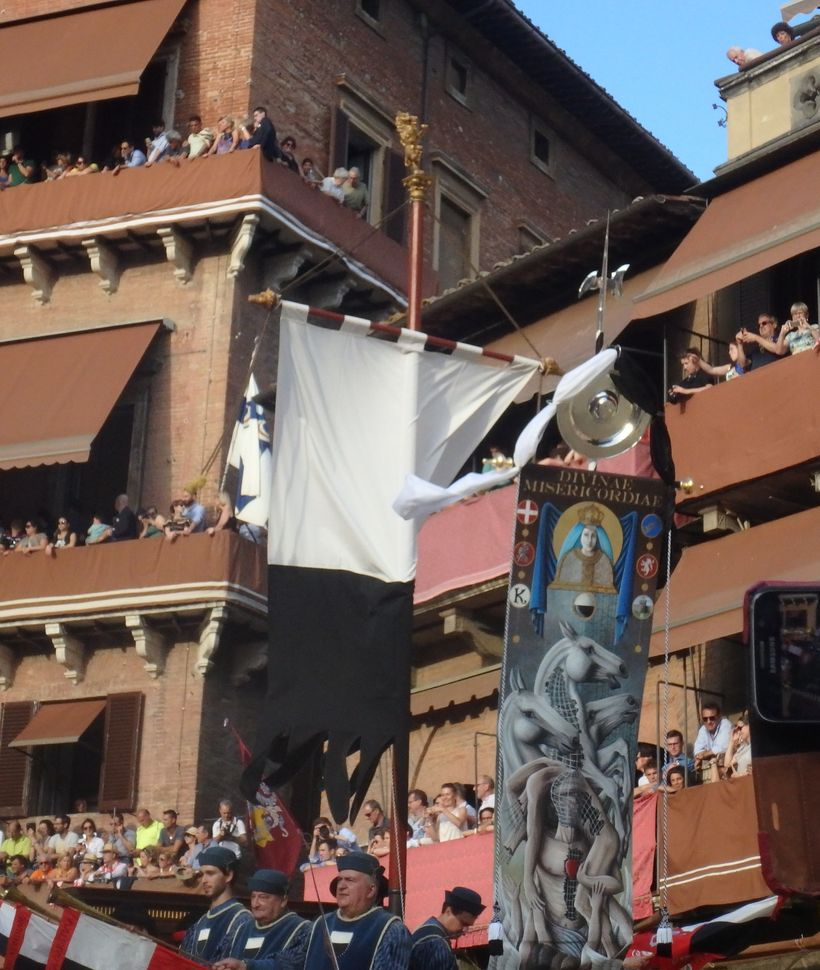 The Palio banner, right, makes it way around the Piazza del Campo in Siena. All the contrada members wave their fazzoletti (s
