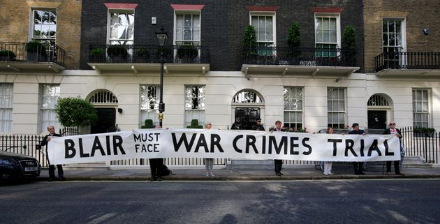 Protesters hold a banner outside the London home of former Prime Minister Tony