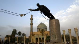A statue of Iraq's President Saddam Hussein falls as it is pulled down in central Baghdad April 9, 2003. U.S. troops pulled down a 20-foot (six metre) high statue of President Saddam Hussein in central Baghdad on Wednesday and Iraqis danced on it in contempt for the man who ruled them with an iron grip for 24 years. In scenes reminiscent of the fall of the Berlin Wall in 1989, Iraqis earlier took a sledgehammer to the marble plinth under the statue of Saddam. Youths had placed a noose around the statue's neck and attached the rope to a U.S. armoured recovery vehicle.