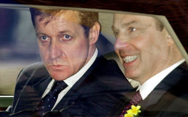 Campbell pictured peering out of Prime Minister Tony Blair's vehicle while he worked for him between...