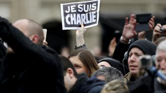 """A person holds up a """"Je Suis Charlie"""" (I am Charlie) sign during a ceremony at Place de la Republique square to pay tribute to the victims of last year's shooting at the French satirical newspaper Charlie Hebdo, in Paris, France, January 10, 2016. France this week commemorates the victims of last year's Islamist militant attacks on satirical weekly Charlie Hebdo and a Jewish supermarket with eulogies, memorial plaques and another cartoon lampooning religion.  REUTERS/Yoan Valat/Pool"""