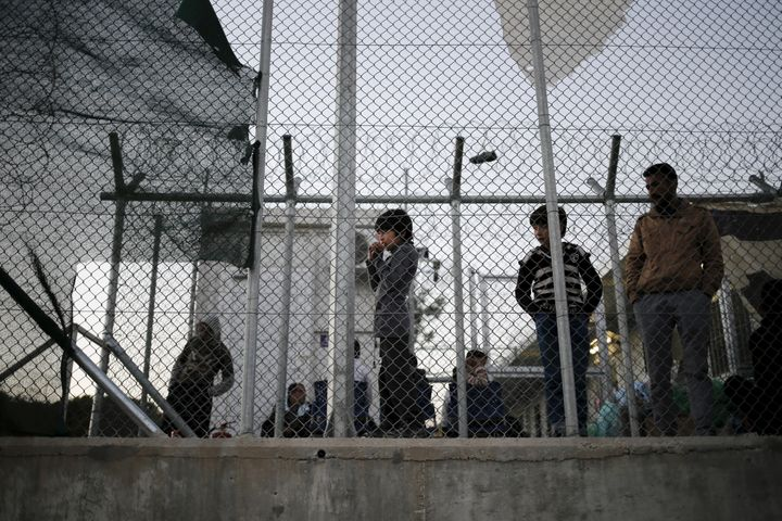 A migrant child stands next to a metal fence at the Moria refugee camp on the Greek island of Lesbos on November 5, 2015. The