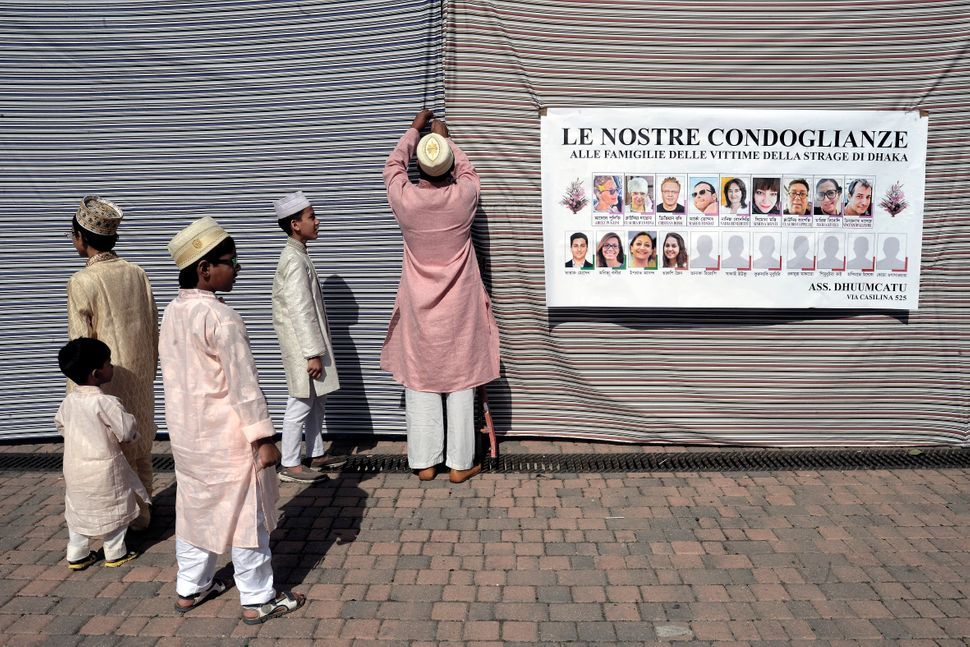 Muslim refugees in Torpignattara, a multiethnic suburb of Rome, display a banner of condolences for the victims of
