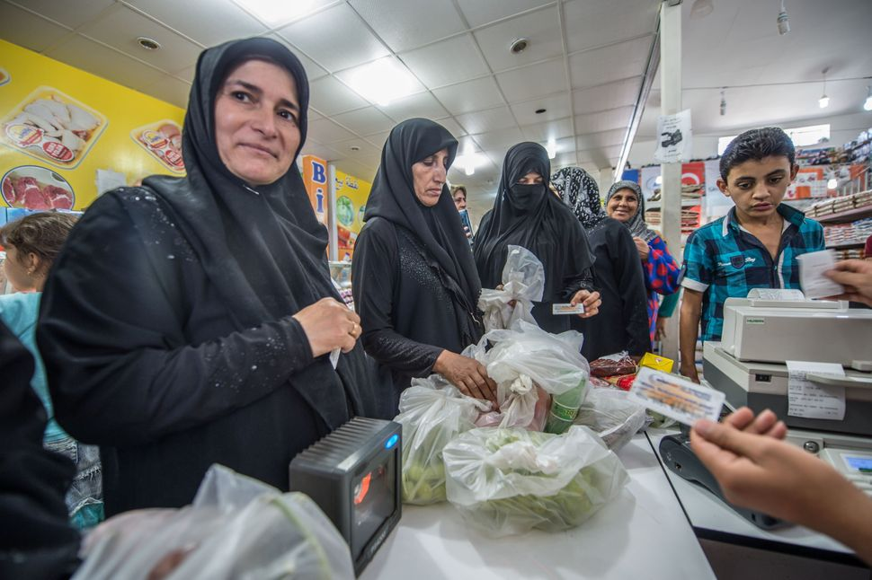 Syrian refugees shop at a camp grocery store in the Suruc district of Sanliurfa, Turkey, on July 1, 2016.