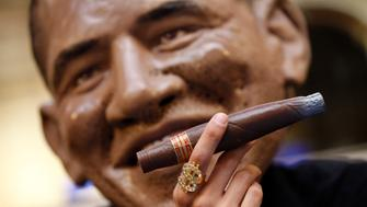 An Oxfam member wears a giant mask representing U.S. President Barack Obama who who holds a cigar and a dollar-sign ring as he sits with G8 summit leaders at a poker table in a gaming parlour in Paris May 23, 2011.  REUTERS/Jacky Naegelen    (FRANCE - Tags: POLITICS)