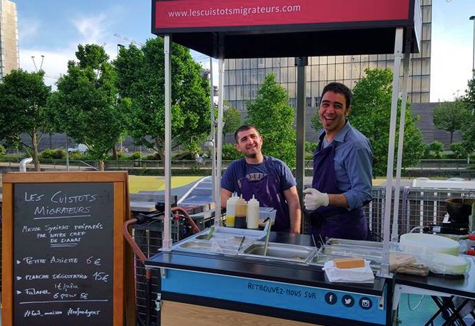 Two Syrian cooks, working for Les Cuistots Migrateurs, serving Syrian appetizers at a Paris venue.