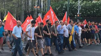 Greek protesters march against austerity, holding the flags of left-wing political factions.