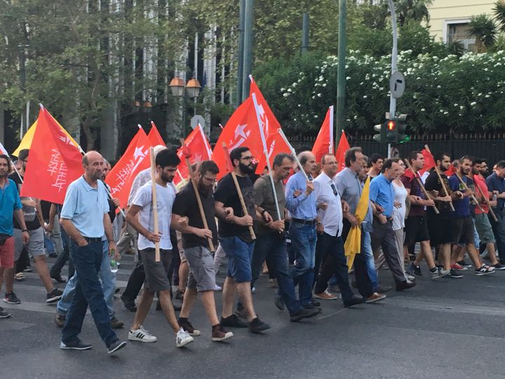 Greek protesters march against austerity, holding the flags of socialist factions.