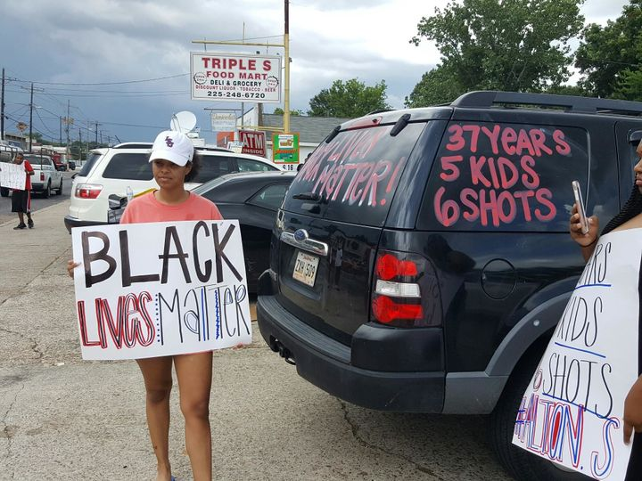A woman outside the Triple S convenience store holds a sign in support of Sterling.