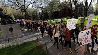 CAMBRIDGE, MA - MAY 9: HearHerHarvard protest walks past the statue of John Harvard in Harvard Yard on Harvard University's campus in Cambridge, Mass., on May 9, 2016. The march began outside Massachusetts Hall and then the march continued around Harvard Yard. (Photo by Barry Chin/The Boston Globe via Getty Images)