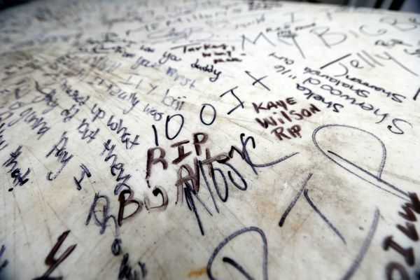 Messages of condolence are written on a table at a makeshift memorial for Sterling.