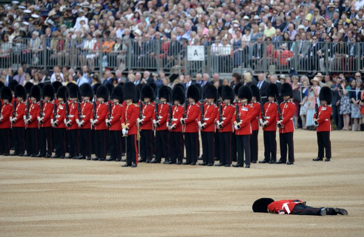 A soldier collapses on Horse Guards Parade ahead of the Queen's Birthday Parade, 'Trooping the Colour', in London on June 11, 2016.