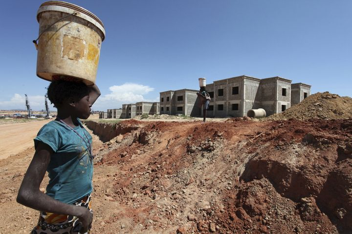 A woman walks past a Chinese construction site in Lubango, Angola.