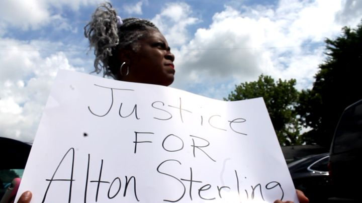 Ivy Early Thomas holds a sign while mourning the death of Alton Sterling, a 37-year-old father of five who was killed by Bato