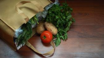 Groceries and produce in a reusable tote on wood