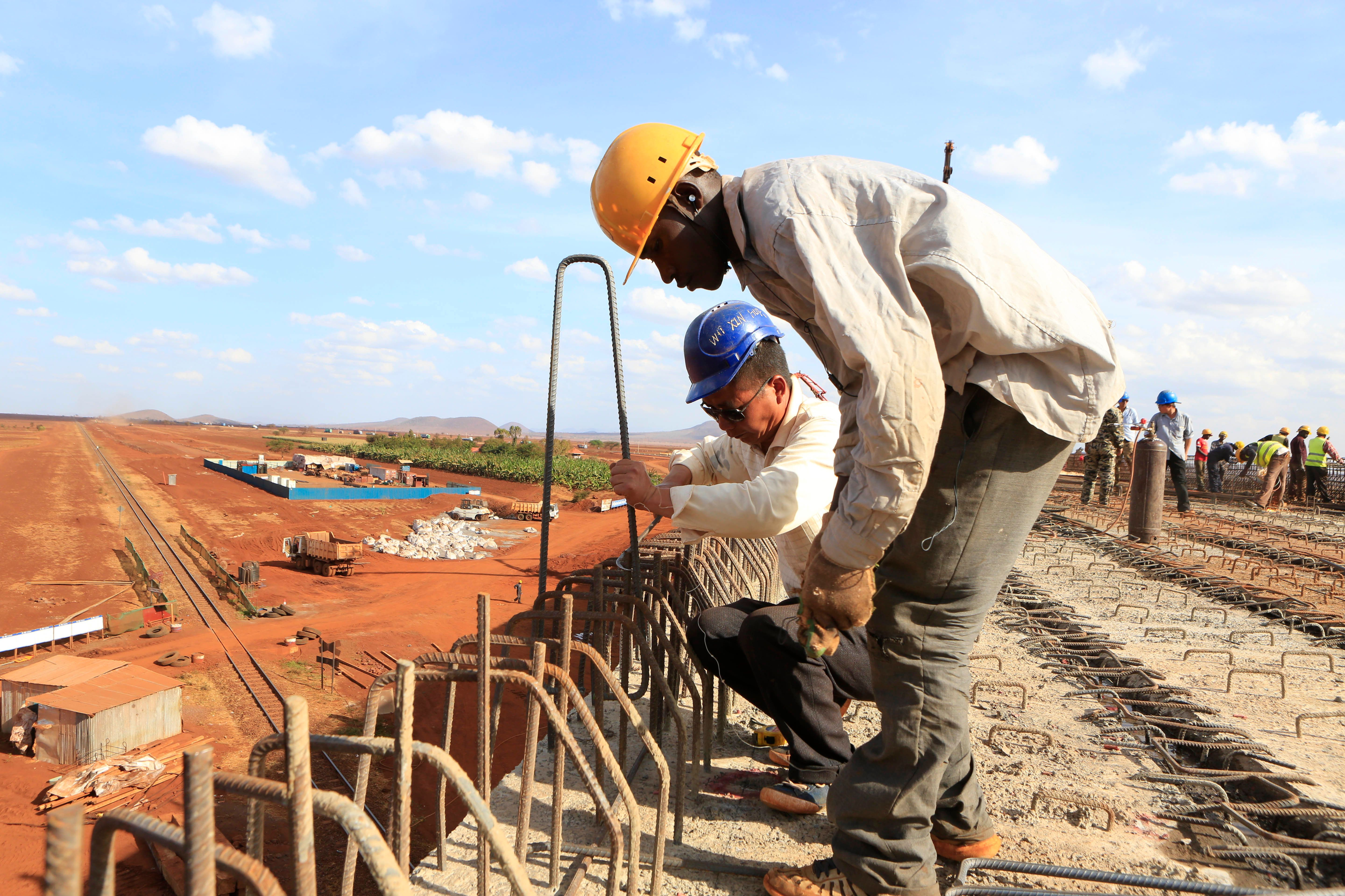 A Chinese engineer and a local construction worker work on a section of the Mombasa-Nairobi standard gauge railway (SGR) in Emali, Kenya October 10, 2015. The China Road and Bridge Corporation (CRBC) tasked with the construction work at a cost of 3.8 billion U.S. dollars is due for completion in mid-2017. REUTERS/Noor Khamis