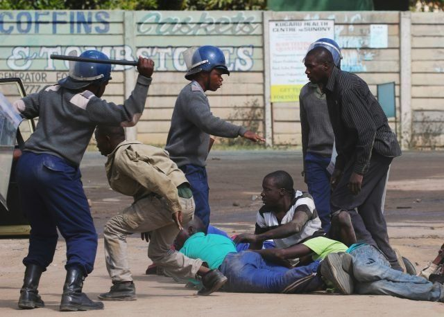 Riot police detain people after a protest by taxi drivers turned violent in Harare on July 4, 2016.
