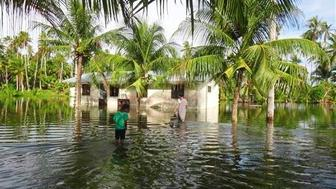 A woman and child walk through knee-deep water to reach their home during a king tide event on Kili in the Marshall Islands. Two king tides in 2015 caused massive flooding over the entire island, leaving thousands of dead fish to rot after the waters receded.