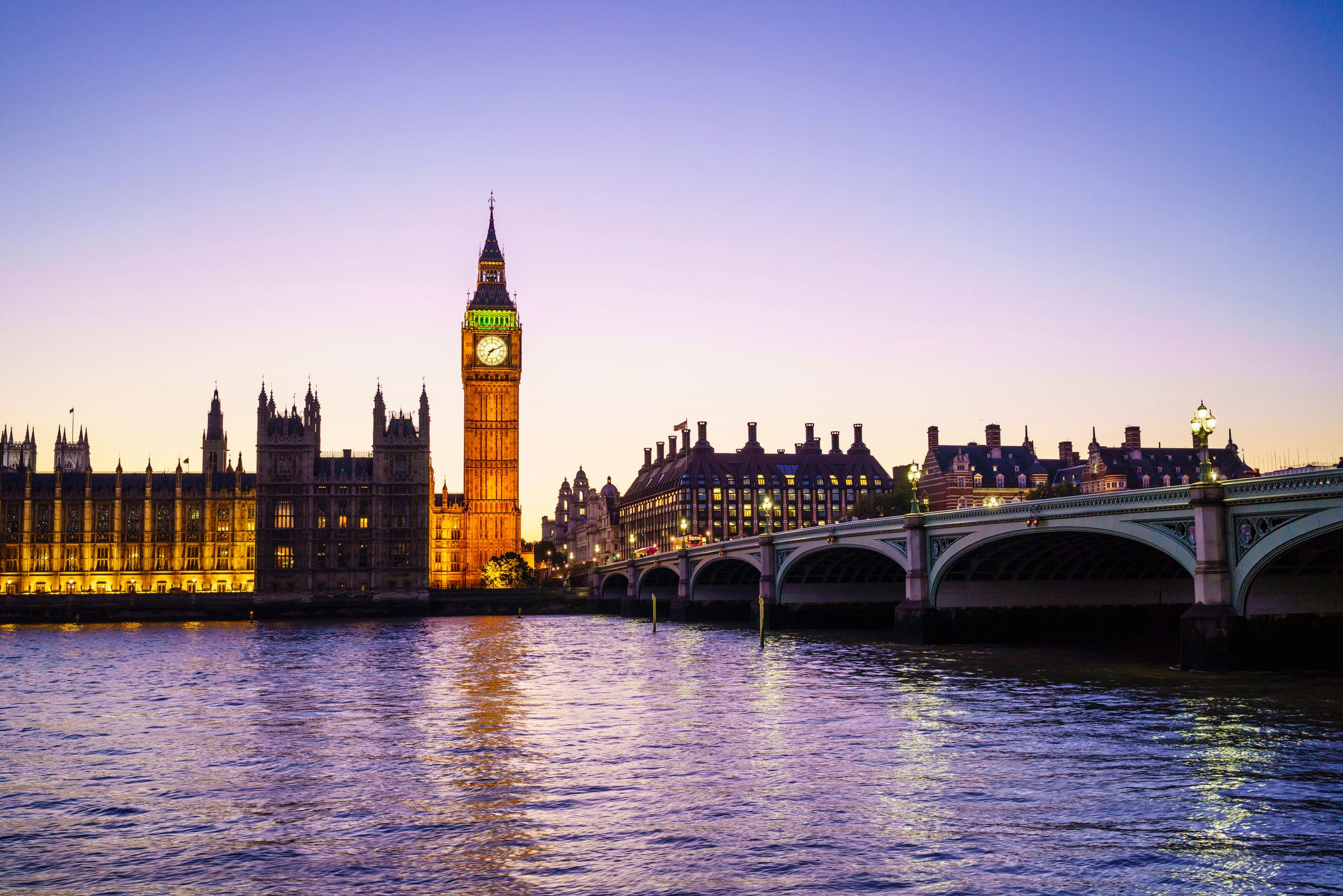 The Houses of Parliament and Big Ben viewed from across the River Thames at dusk.