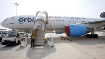 A security guard stands next to the ORBIS International aircraft, housing the world's only Flying Eye Hospital (FEH), at Noi Bao international airport in Hanoi, Vietnam June 2, 2015. The flying hospital, the world's only accredited ophthalmic training hospital aboard a DC-10 aircraft, is in Vietnam to deliver a two-week national ophthalmic training, according to a press release. REUTERS/Kham
