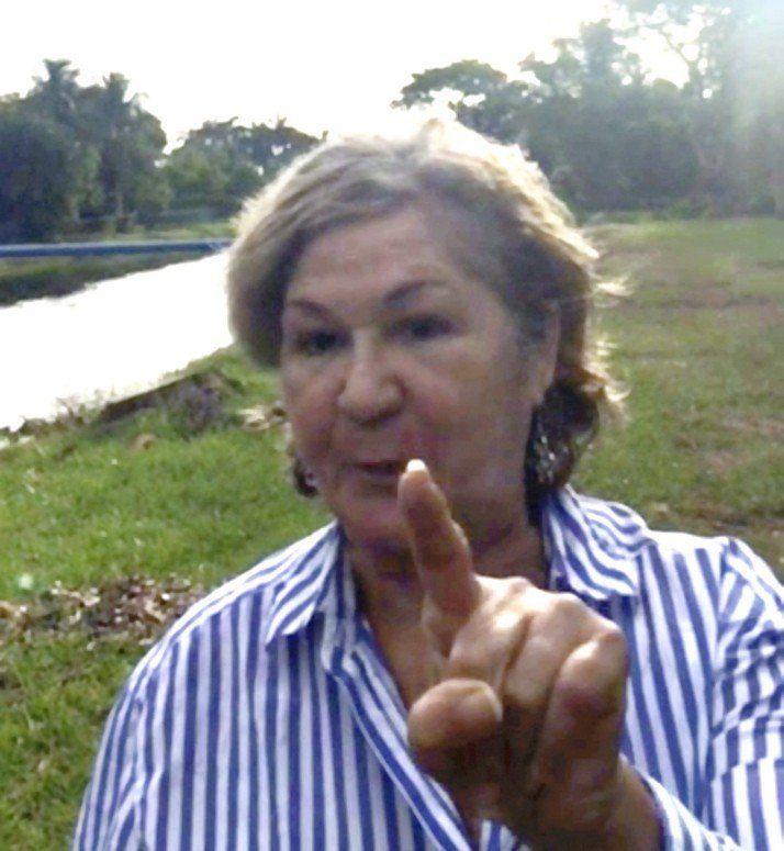 Maria Dorrbecker waves her finger at Rayne Burse, an African American woman walking her dog in her new neighborhood.