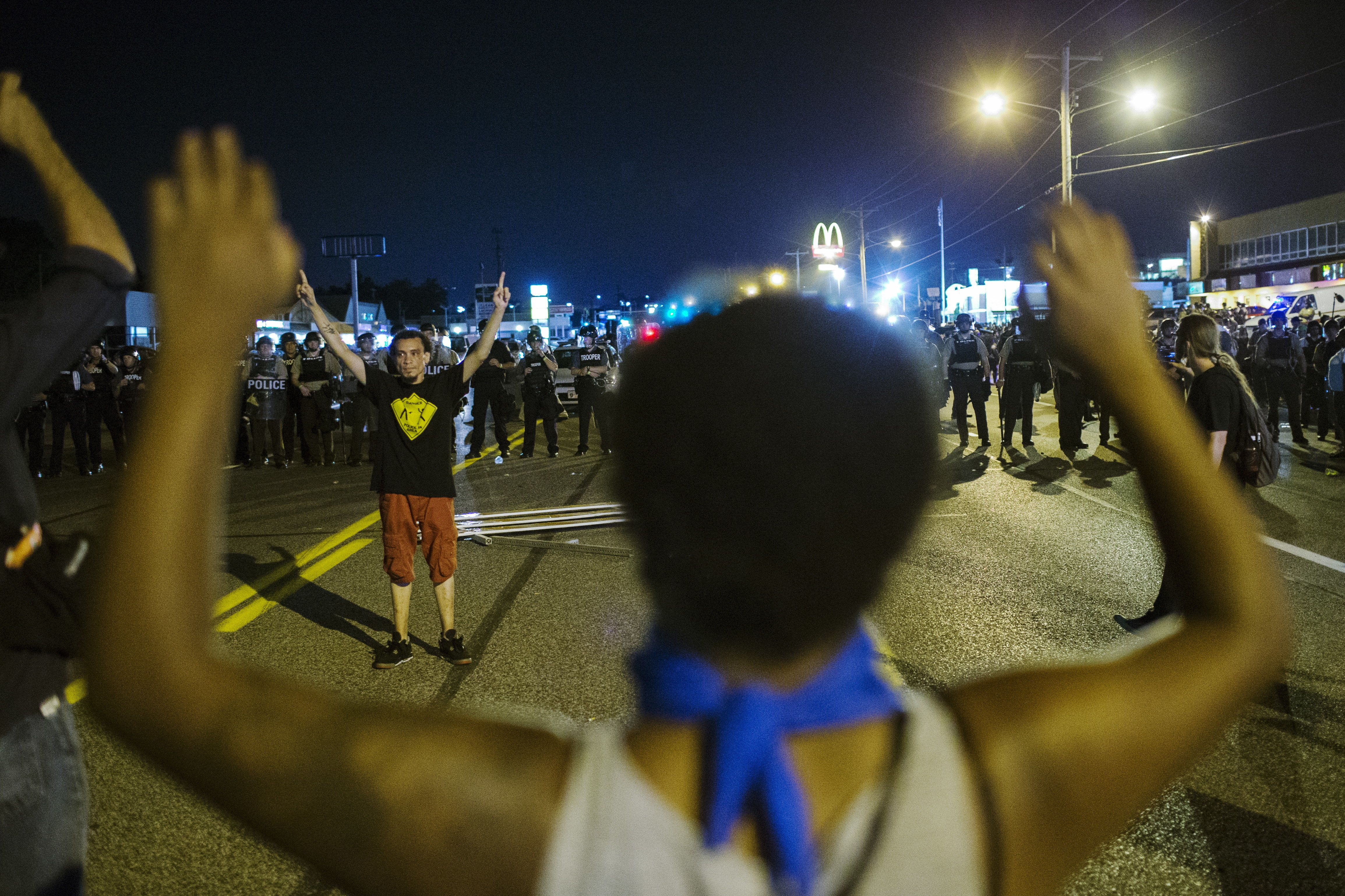 Anti-police demonstrators gesture at a line of St Louis County police officers during protests in Ferguson, Missouri August 11, 2015. Police in riot gear clashed with protesters who had gathered in the streets of Ferguson early on Tuesday to mark the anniversary of the police shooting of an unarmed black teen whose death sparked a national outcry over race relations. REUTERS/Lucas Jackson