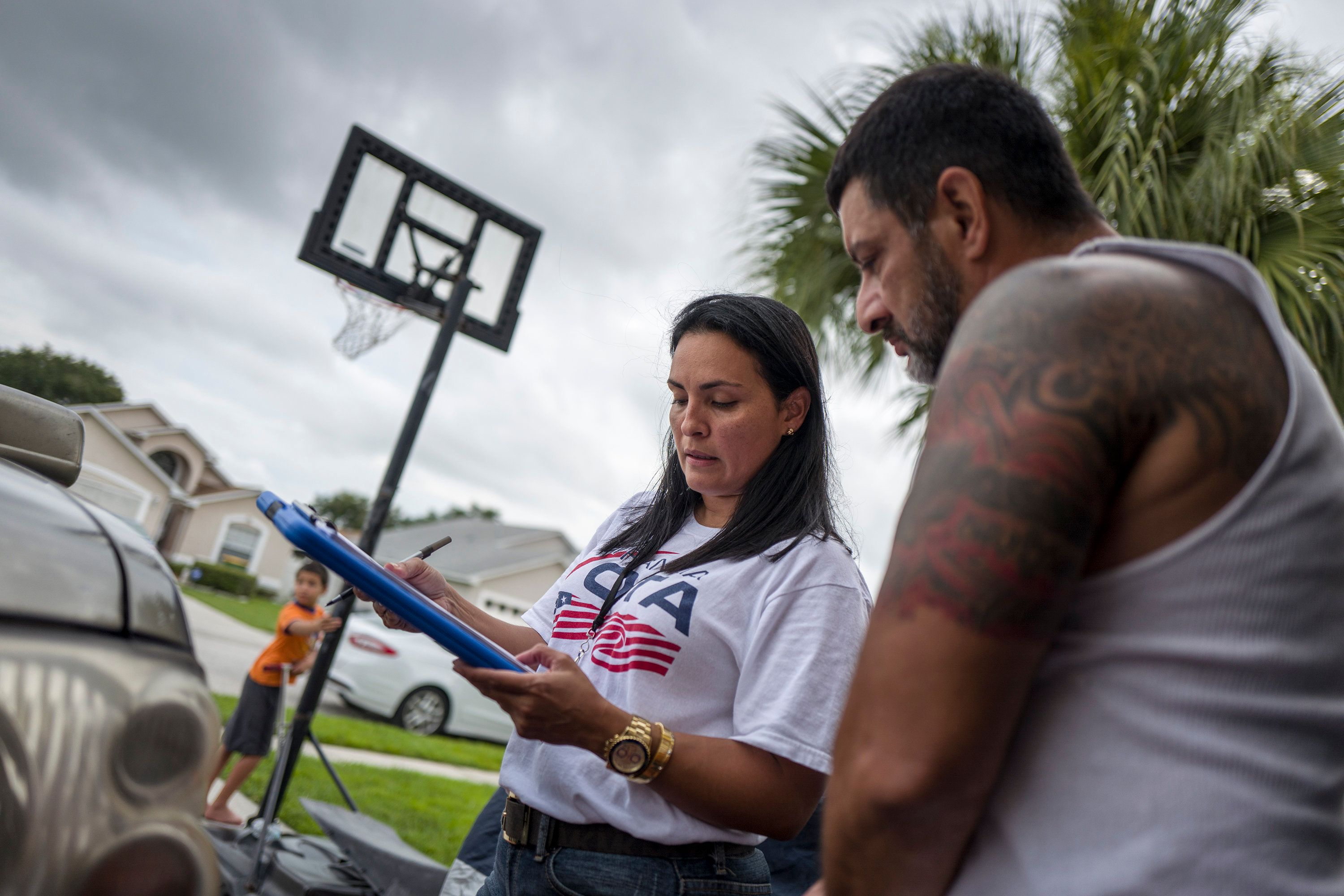 KISSIMMEE, FL - JULY 24: Soraya Marquez, the state coordinator for Mi Familia Vota and her crew hit a Puerto Rican neighborhood trying to get Latinos to register to vote in the 2016 presidential election on July 24, 2015 in Kissimmee, FL.  One of the crew, Mairy Reyes manages to persuade a man originally from Brooklyn to register to vote outside of his house in Kissimmee. (Photos by Charles Ommanney/The Washington Post via Getty Images)